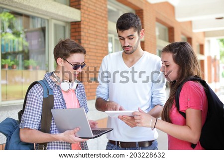 Happy College students using tablet pc and computer on campus, caucasian