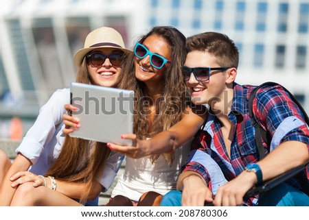 Happy College students using tablet pc on campus - stock photo