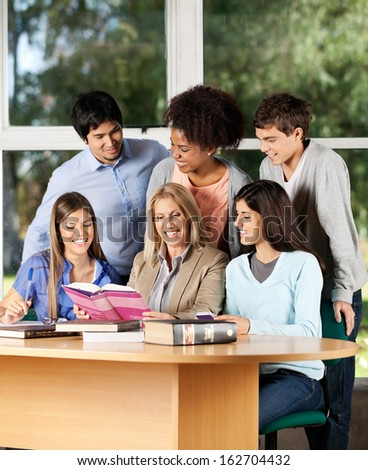 Happy college teacher with book explaining lesson to group of students in classroom - stock photo