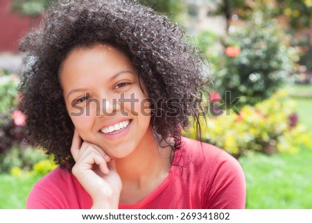 Happy colombian woman outside in a park - stock photo