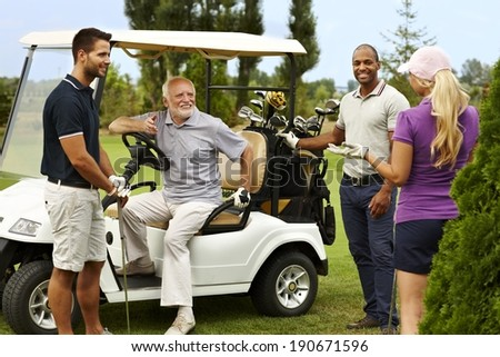 Happy companionship ready for golfing around golf cart. - stock photo