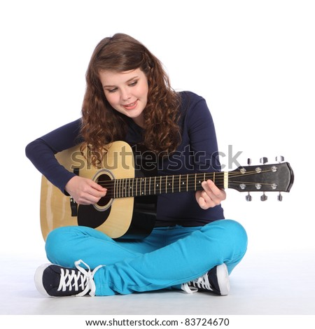 Happy concentration from pretty teenager girl sitting on floor playing music on acoustic guitar. She is wearing bright blue trousers and navy top. - stock photo