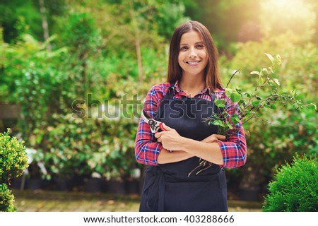 Happy confident attractive young woman pruning plants in a nursery as she celebrates her success as an entrepreneur with her own business - stock photo