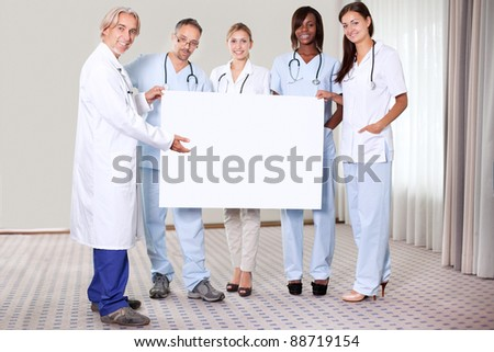Happy confident group of doctors holding a blank placard pointing towards copy space - stock photo