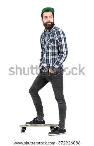 Happy confident hipster with hands in pocket wearing baseball cap standing on longboard side view. Full body length portrait isolated over white studio background.