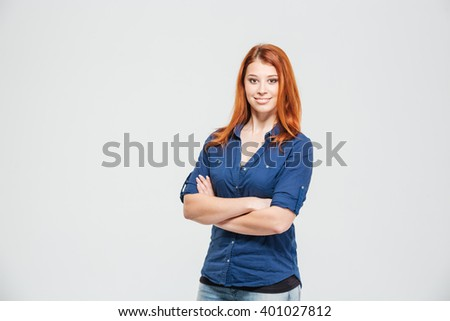 Happy confident redhead young woman standing with arms crossed over white background - stock photo