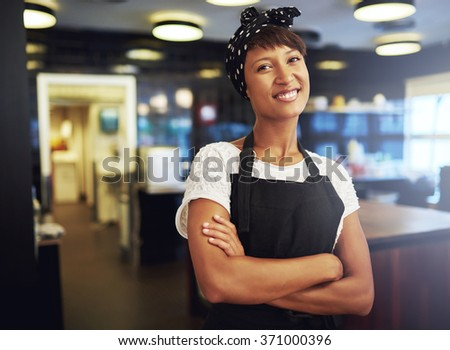 Happy confident young African American small business owner standing in her shop with folded arms smiling at the camera - stock photo