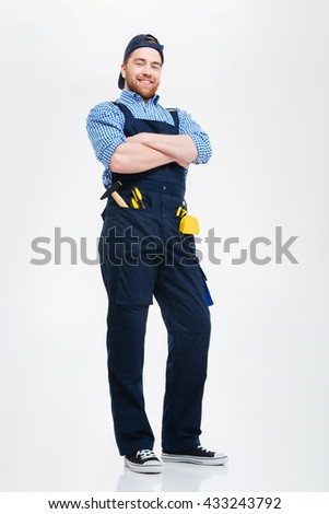 Happy confident young builder standing with arms crossed - stock photo