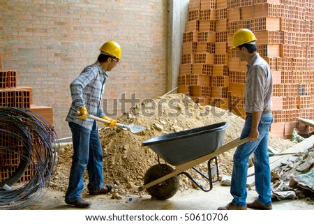 Happy construction workers wearing helmets and working - teamwork concepts - stock photo