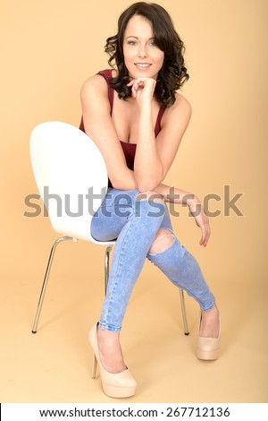 Happy Content Pleased Young Woman Sitting on a White Chair With Her Legs Crossed - stock photo
