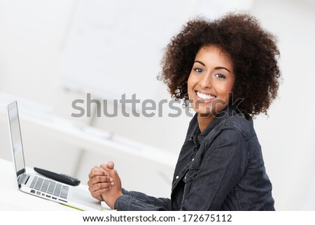 Happy contented young African American woman with an afro hairstyle sitting at her desk in front of a laptop computer turning to smile at the camera - stock photo