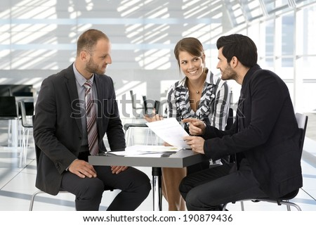 Happy corporate business people having discussion by coffee table. - stock photo