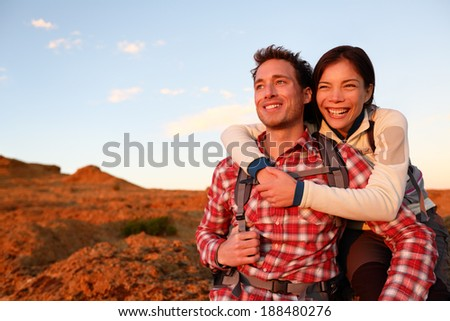Happy couple active lifestyle hiking enjoying outdoors activity. Smiling laughing young lovers embracing looking at sunset during hike. Cheerful interracial couple, Asian woman, Caucasian man. - stock photo