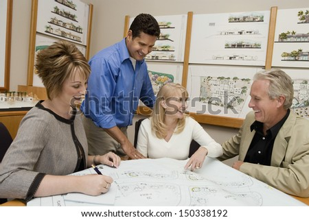 Happy couple and architects discussing plan for new house in office - stock photo