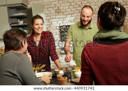 Happy couple and friends talking and cooking together in kitchen. - stock photo