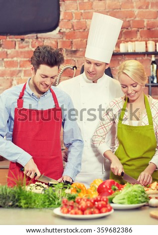 happy couple and male chef cook cooking in kitchen - stock photo