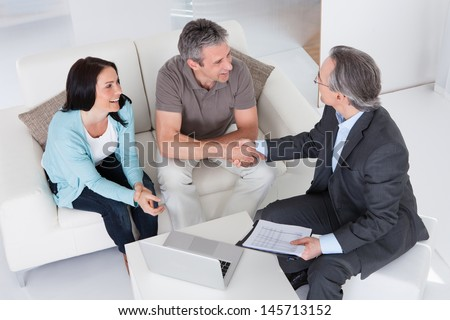 Happy Couple And Mature Consultant Discussing Together - stock photo
