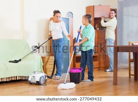 Happy couple and teenager boy vacuuming in living room