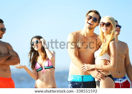 Happy couple and their playful friends relaxing at the beach, on blue sky background