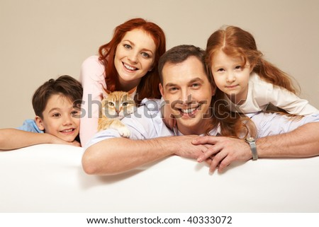 Happy couple and their two children smiling with pet among them - stock photo