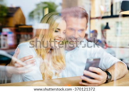 Happy couple at coffee shop browsing internet on smartphone - stock photo