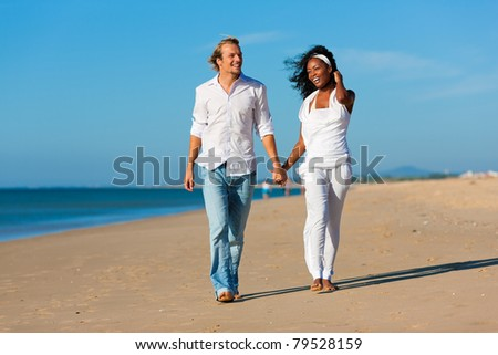 Happy couple - black woman and Caucasian man - walking and running down a beach in their vacation - stock photo