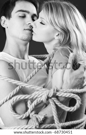 Happy couple bound with ropes. Cord fastened by a bow - stock photo