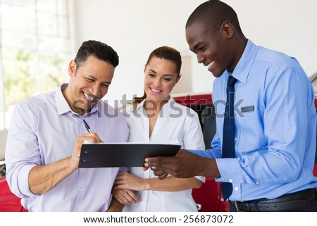 happy couple buying a new car at vehicle showroom - stock photo