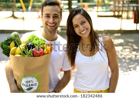 Happy couple carrying a shopping paper bag full of organic food.