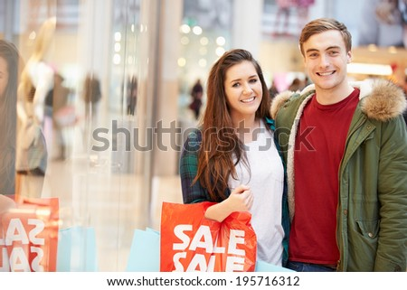 Happy Couple Carrying Bags In Shopping Mall - stock photo