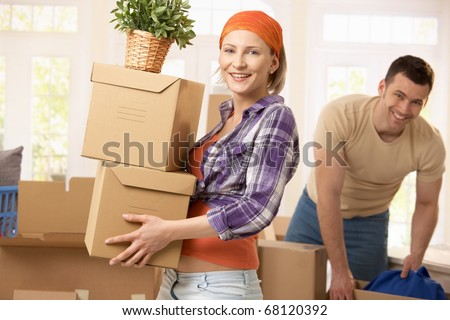 Happy couple carrying boxes at moving house. - stock photo