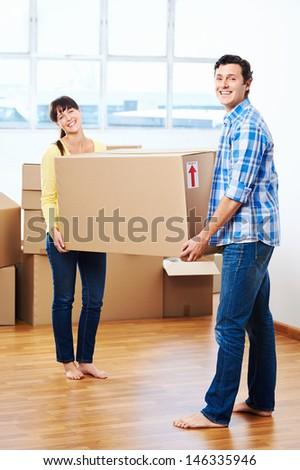 Happy couple carrying boxes moving into new home apartment house - stock photo