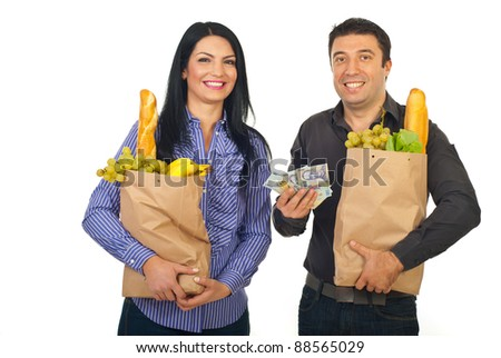 Happy couple carrying shopping paper bags with food and showing money banknotes  isolated on white background - stock photo