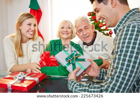 Happy couple celebrating christmas eve with gifts and seniors - stock photo