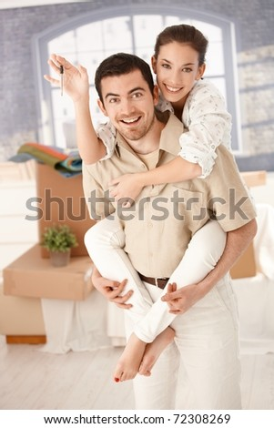 Happy couple celebrating new home, smiling, holding keys in hand.?