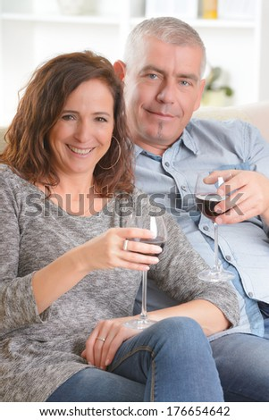 Happy couple celebrating with wine in hands in home