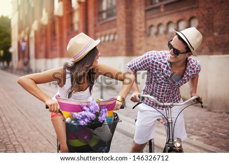 Happy couple chasing on bike in the street - stock photo