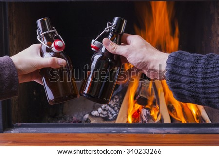 happy couple cheering with beer bottles at skiing hut - stock photo