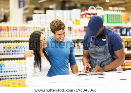 happy couple choosing paint color at hardware store with help of the shop assistant - stock photo