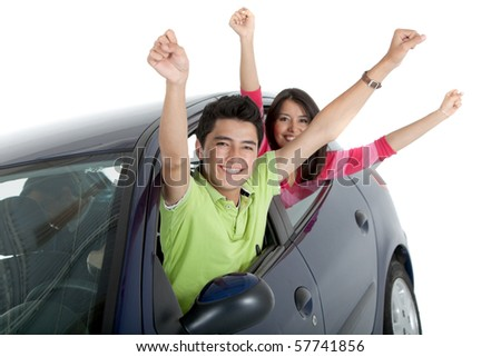 Happy couple coming out of the windows of a car - isolated over a white background - stock photo