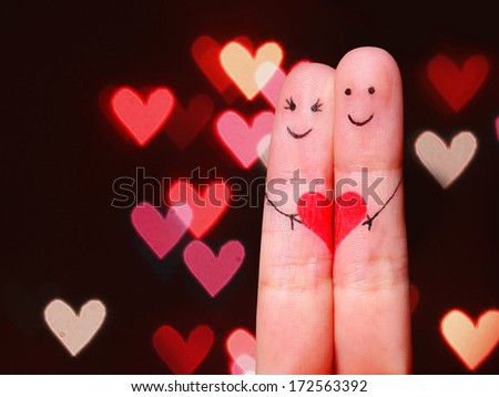 Happy Couple Concept. Two fingers in love with painted smiley faces and heart over bokeh background - stock photo