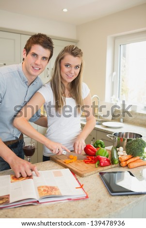 Happy couple cooking together in kitchen - stock photo
