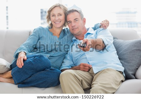 Happy couple cuddling and sitting on the couch watching tv at home in the living room - stock photo