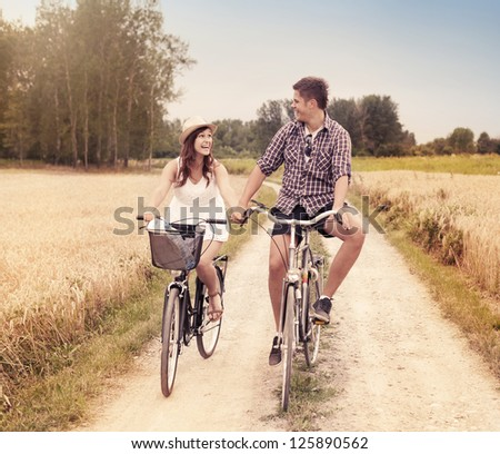 Happy couple cycling outdoors in summer - stock photo
