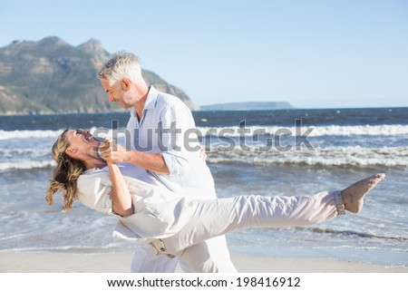 Happy couple dancing on the beach together on a sunny day - stock photo
