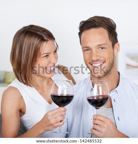 Happy couple dating with red wine at home - stock photo