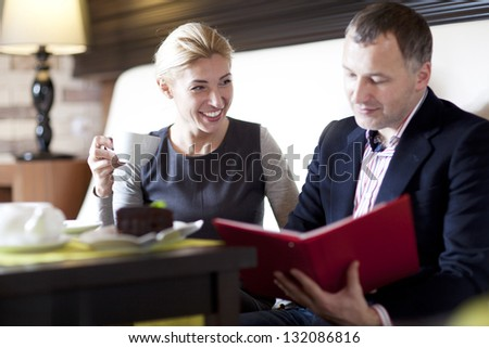 happy couple dining out in restaurant and reading menu