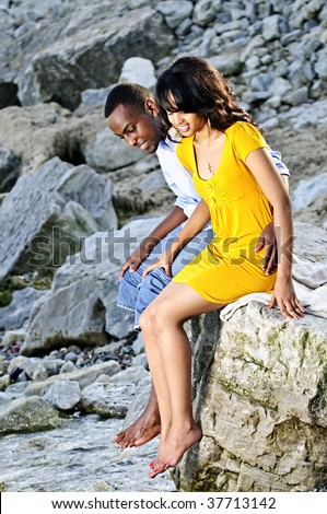 Happy couple dipping feet in ocean sitting on boulder at rocky shore - stock photo