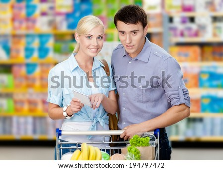 Happy couple discussing the shopping list and chosen products standing near the shopping trolley full of food - stock photo