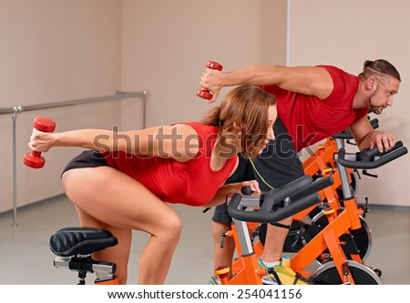 Happy couple doing indoor biking in a fitness club - stock photo